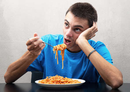 an young man eating spaghetti with inappetence