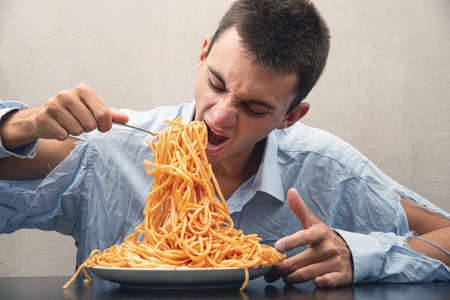 a man eating spaghetti with tomato sauce