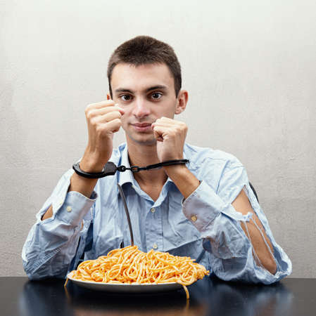 an young man eating spaghetti handcuffed Archivio Fotografico
