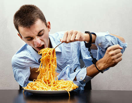 an young man eating spaghetti handcuffed 免版税图像