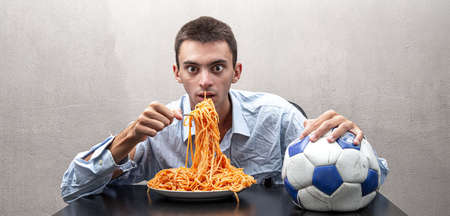 an young man eating spaghetti caught in football 免版税图像