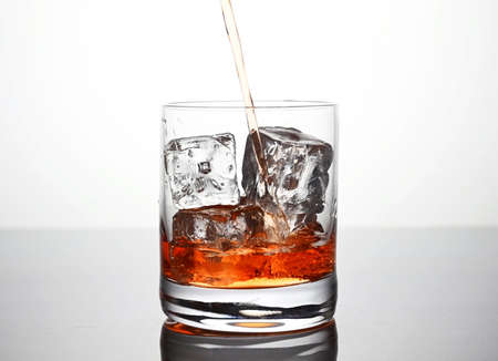 a glass with ice and liquor splash