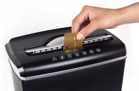 Female hand cutting or shredding a gold credit card with a black shredder isolated with copy space on white background  photo