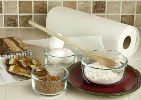 utencils: Cook Book with baking tools and ingredients including flour brown sugar eggs in glass bowls set up on kitchen counter against tiled back spash