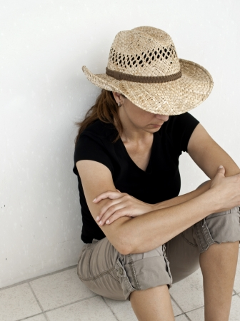 dissapointed: Depressed and Dissapointed Young Women sitting on the tile floor with back against wall with straw hat outside with copy space  Stock Photo