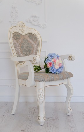 antique chair: A white antique chair with a blue flower bouqet lying on it Stock Photo