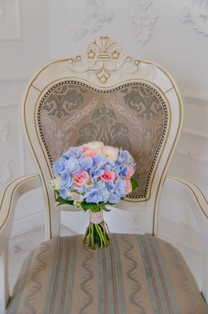 bouqet: A white antique chair with a blue flower bouqet lying on it Stock Photo