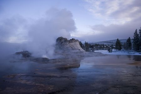 Evening shot of Castle Geyser with the moon behind the stream vent  Stock Photo