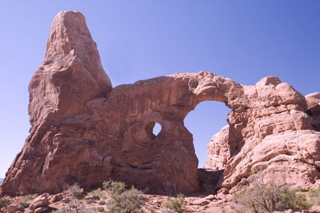 A large beautiful pink arch against a blue sky