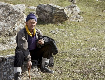 This Normadic sheepherder stops for a rest before moving his sheep down the hill.