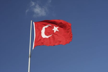 Against the blue sky flies  the red and white Turkish flag Stock Photo
