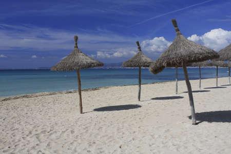 Beach in Mallorca Spain.  Sun umbrellas on the beach in Mallorca Spain