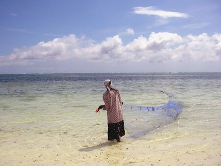 Woman fishing in the Indian Ocean from the island of Zanzibar Tanzania