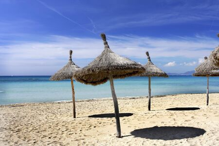Sun umbrellas on the beach in Mallorca Spain Stock Photo