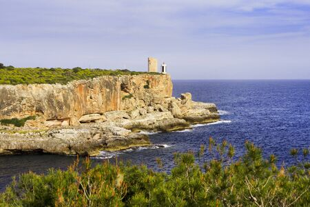 Lighthouse on rocky cliff in Mallorca Spain Stock Photo