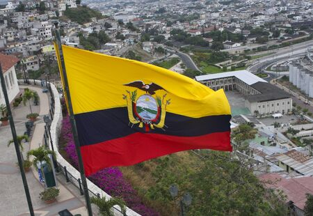 An Ecuadorian flag with yellow, blue and red strips flying over a city in Ecuador, South America