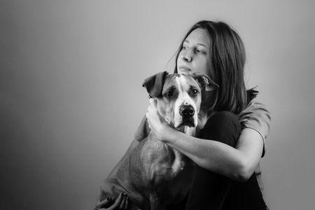 monocrome: Monocrome image of a girl hugging her staffordshire terrier dog.
