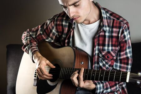 Male musician in casual wear plays acoustic instrument and holds pick in mouth