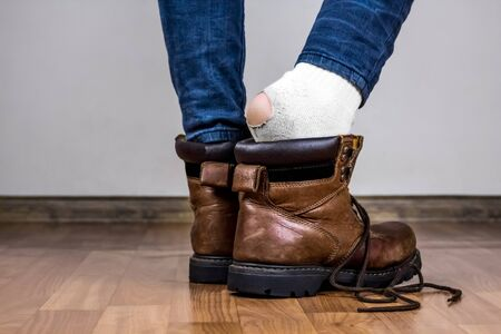 heelpiece: Taking of boots and finding out the hole in the sock. Stock Photo