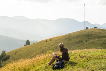 Hiker female uses portable tablet pc in mountains near cellphone tower Stock Photo
