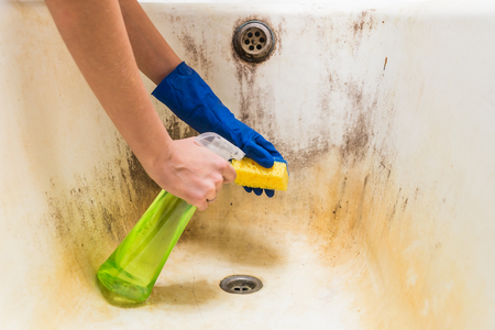 Female hands in gloves clean dirty old bathtub with corrosion and mould with detersive Stockfoto