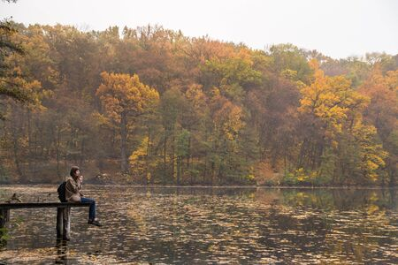 Girl enjoys rest and drinks coffee near the lake at nature park on gold mellow autumn day