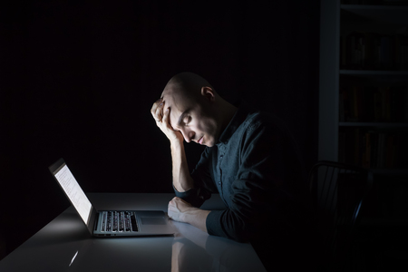 Tired or exhausted man at computer late in the evening with closed eyes. Portrait of young male person working or studying at laptop at night - concept of depression, stress, overwork and pressure at work or study