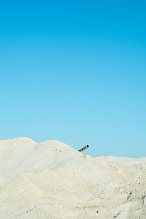 White sands, blue sky and rusty pipe. Abstract concept image of waste land with sandhill and clear sunny sky