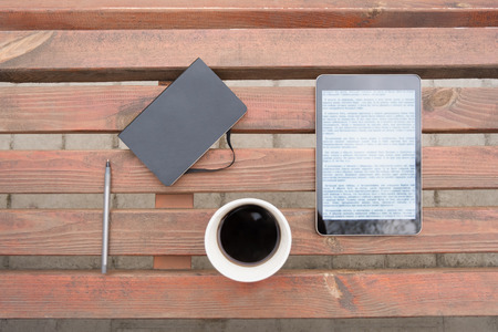 Business outdoor flat lay. Top view of note pad, pen, black coffee cup and tablet computer at wooden bench in a park