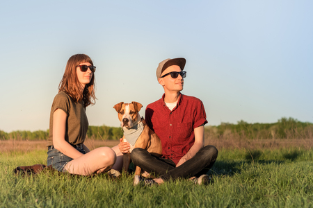 Young happy couple of man and woman with staffordshire terrier dog sit at lawn. Two persons in casual clothes hug adopted pitbull dog in bandana and enjoy beautiful sunny afternoon in spring or summer
