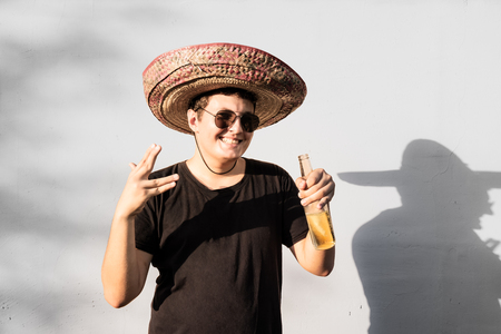 Young male person in sombrero holding bottle of drink. Mexico independence festive concept of man wearing national mexican hat partying