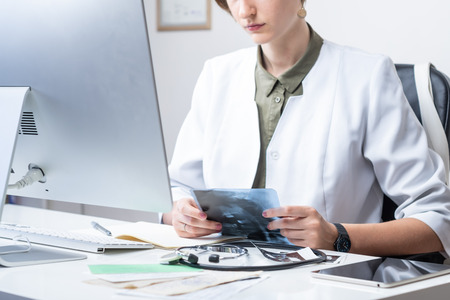 Female physician at modern medical doctor office. Woman examining x-ray at workplace in front of a desktop computer Stock fotó