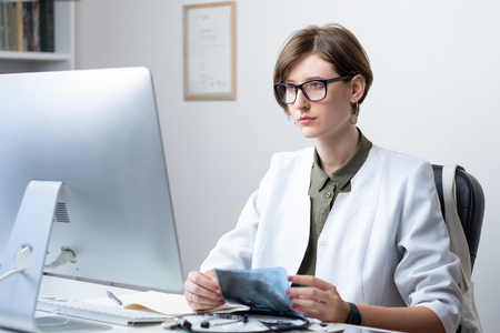 Female practitioner at modern medical doctor office. Young medical doctor examining x-ray at workplace in front of a desktop computer