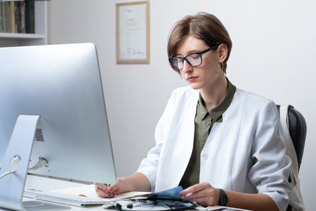 Female practitioner working at modern medical doctor office. Young medical doctor taking notes at workplace in front of a desktop computer Stock fotó