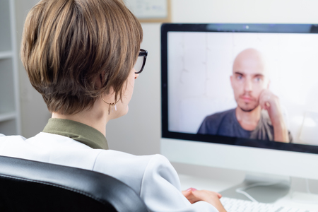 Digital health concept: practicing physician having online meeting with a patient. Medical doctor consulting a person by means of web conference system