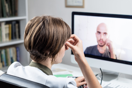 Digital health concept: practicing physician having online appointment with a patient. Medical doctor consulting a person by means of web conference system