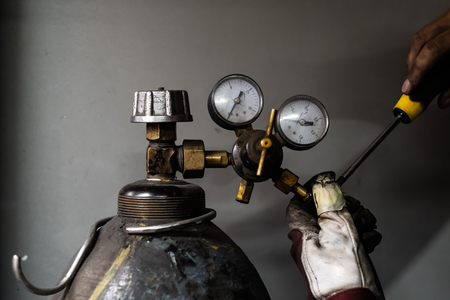 Fixing a propane gas tank. Male hands repairing a compressed cylinder of liquid gas for welding 스톡 콘텐츠