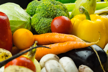 Close-up image of fresh organic vegetables. Locally grown bell pepper, corn, carrot, mushrooms and other natural vegan food laying on table.