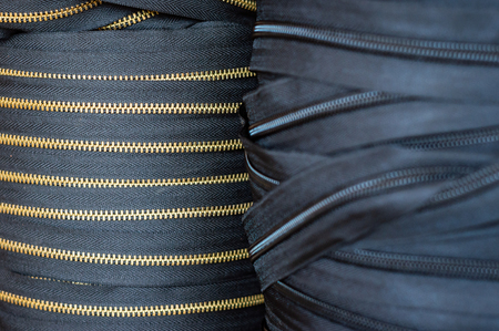 Huge rolls of zippers. Laps of black and gold metal furnishing for clothing or goods making manufacture