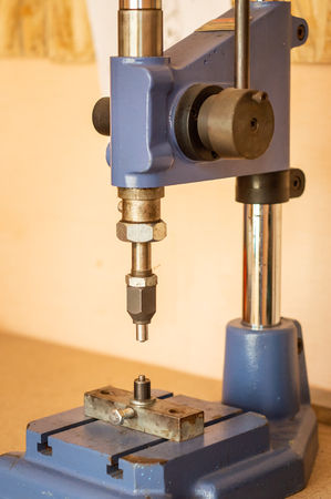 Pressing machine in clothes and accessories manufacture. Clench installing device at workshop