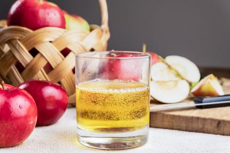 素朴な木製のテーブルの上にシドレドリンクと熟したジューシーなリンゴのクローズアップ画像。自家製サイダーと地元産の有機リンゴのグラス