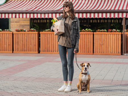 Young pretty woman with dog holds paper bag of groceries in front of market place or vegetable store. Going to shop for food with trained pitbull terrier puppy Stock fotó