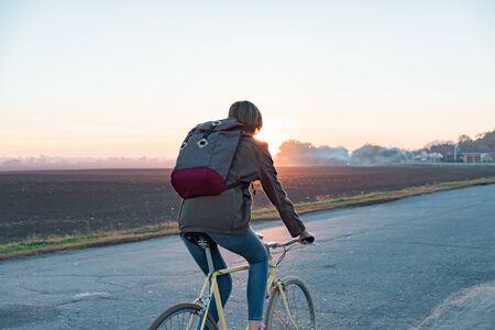 Female commuter riding a bike out of town to a suburban area. Young woman goes home by bike from work along the road at sunset