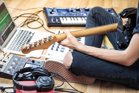 Male guitarist playing electric guitar at modern home studio or rehearsal room. Young man producing music with electronic effects processors, synthesizer and laptop