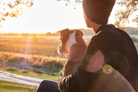 Hugging a dog in beautiful nature at sunset. Woman facing evening sun sits with her pet next to her and enjoys beauty of nature