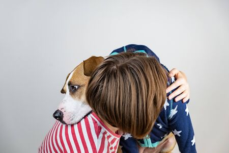 Love and kindness to animals concept. Woman hugs her dog in studio background