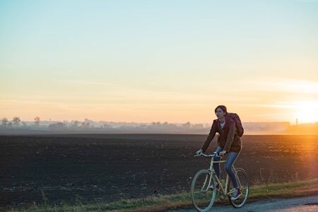 Female commuter riding a bike out of town in rural area. Young woman riding bike at sunset