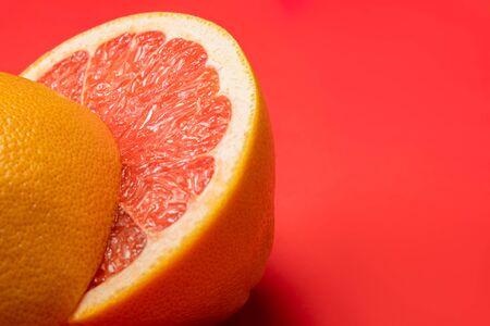 Grapefruit cut in half on vivid red background, copy space. Fruitarianism, vegetarian or vegan food: close-up view of fresh and ripe citrus fruit in bright colors 版權商用圖片