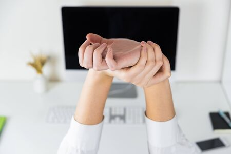 Stretching arms in sparse office workplace. Hands of an employee in front of modern desktop, overwork and tiredness concept