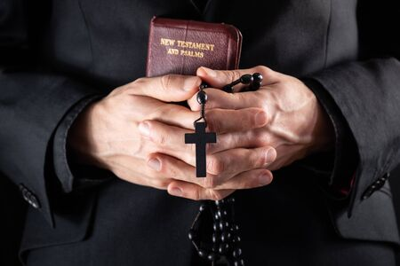 Hands of a christian priest dressed in black holding a crucifix and New Testament book. Religious person with Bible and prayer beads, low-key image.